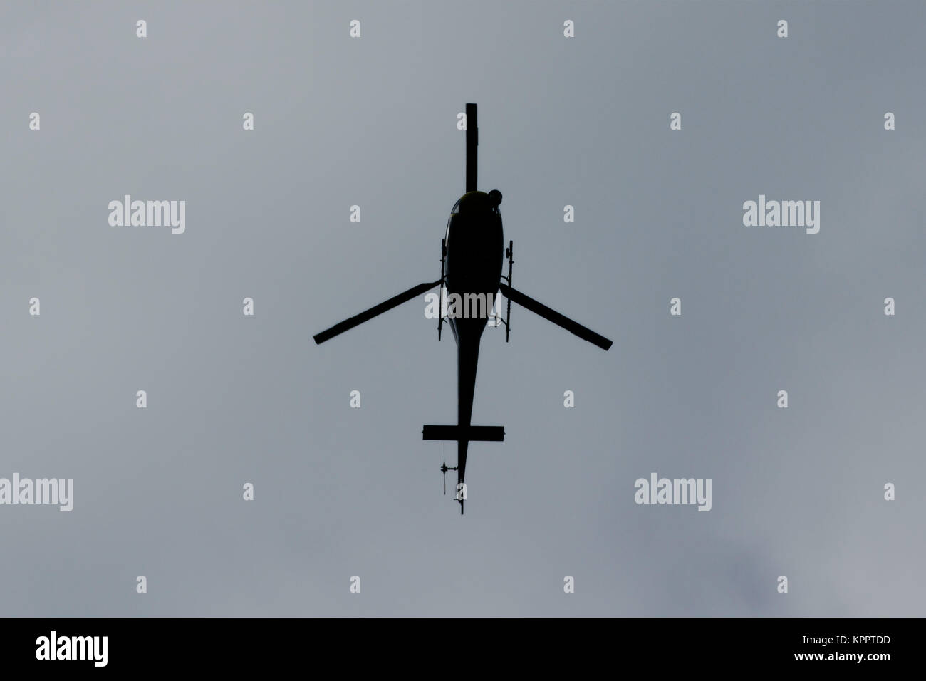 Police Scotland helicopter from the air support unit, in flight, hovering in the sky above Glasgow, Scotland - Stock Image