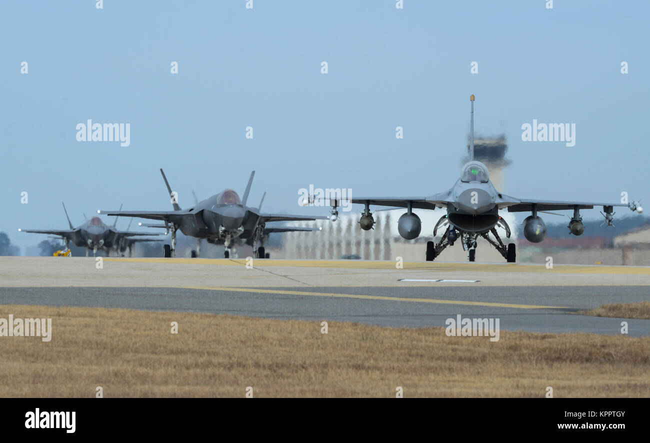 A U.S. Air Force F-16 Fighting Falcon and four F-35A Lightning IIs assigned to the 34th Expeditionary Fighter Squadron Stock Photo
