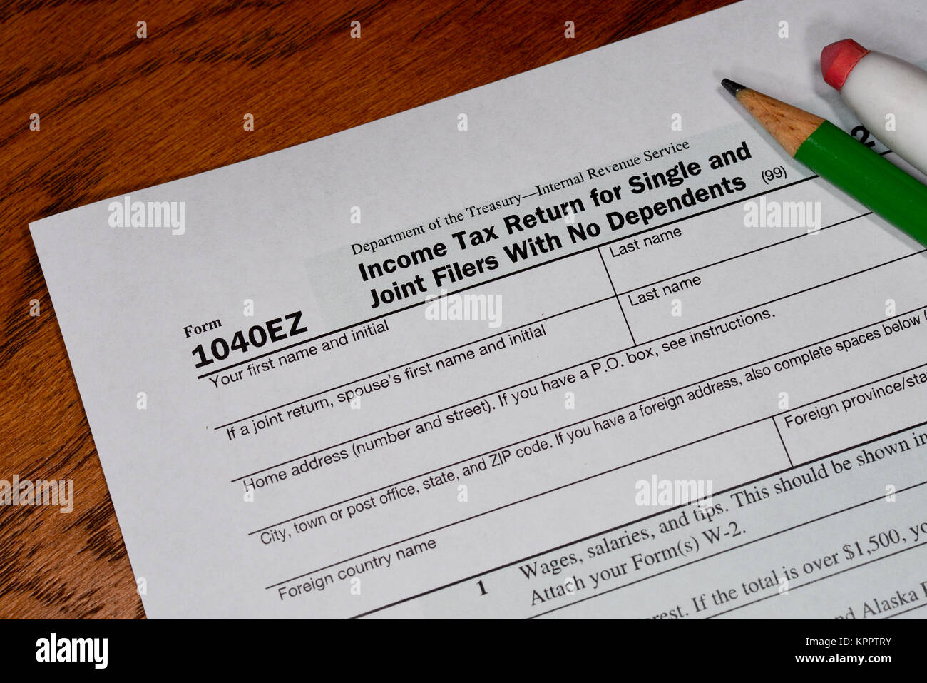 Simple version of the US income tax form for individuals - Form 1040EZ - with a pencil and an eraser on a wooden - Stock Image
