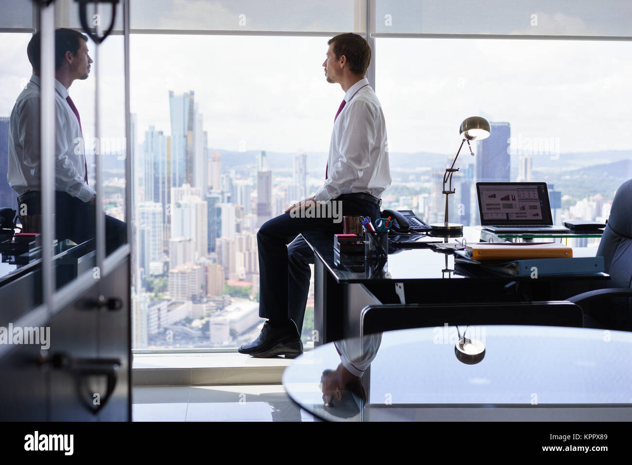 Business Person Sits On Desk Looking Out Of Office Window - Stock Image