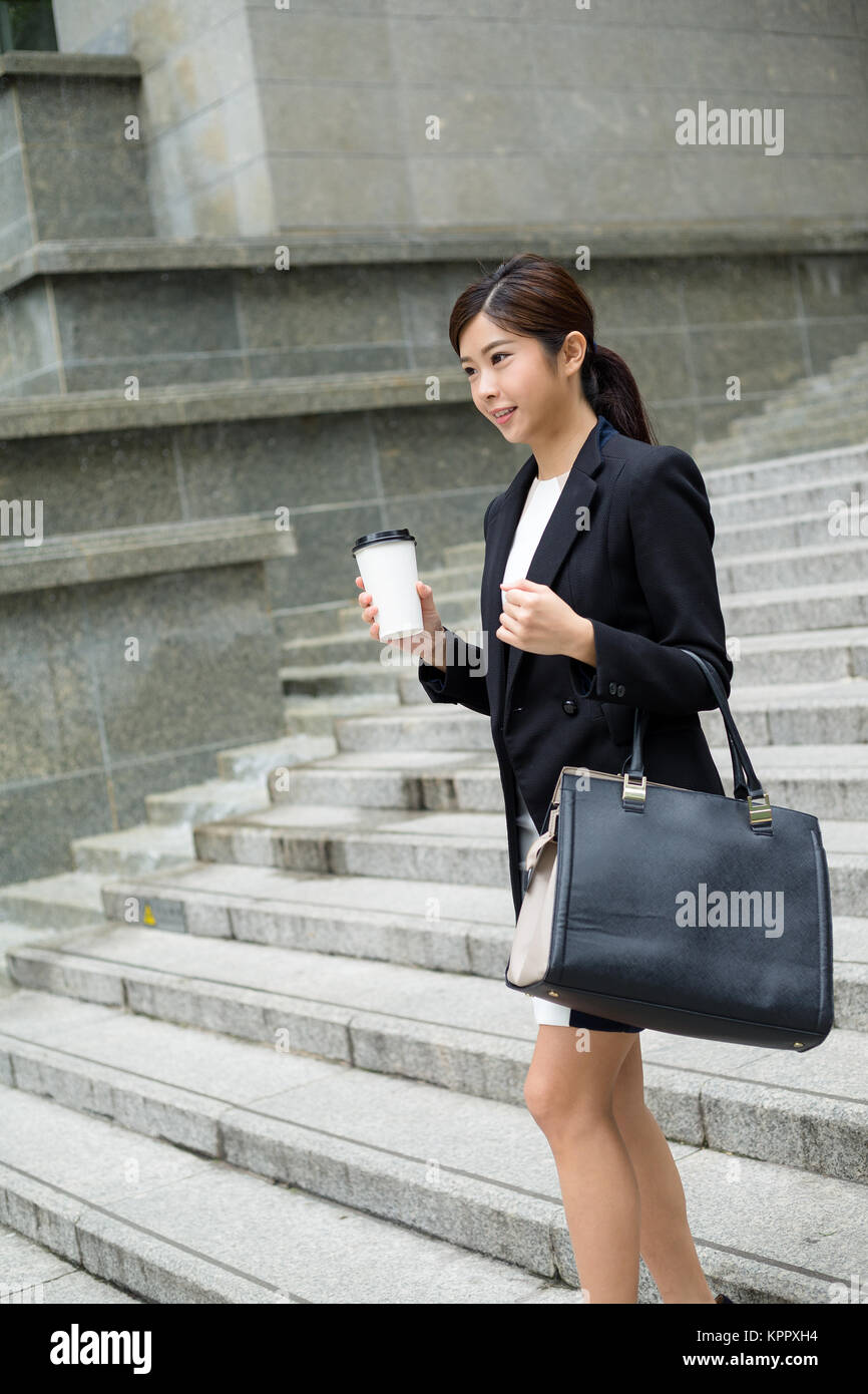 Businesswoman walking out of office - Stock Image