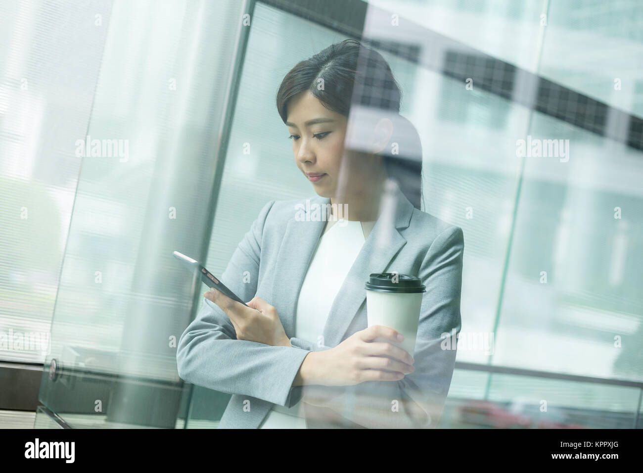Businesswoman use of mobile phone inside office building - Stock Image