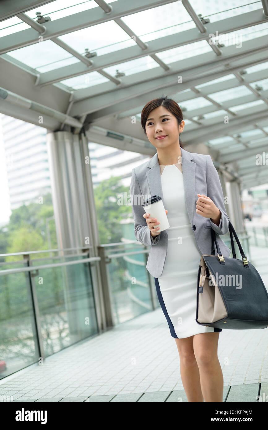 Businesswoman walking at street - Stock Image