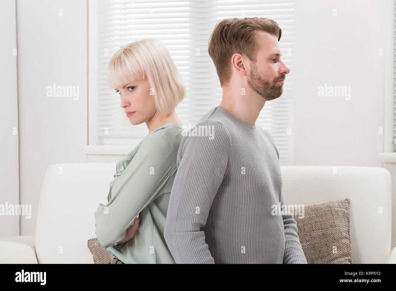 Couple Sitting Back To Back On Couch - Stock Image