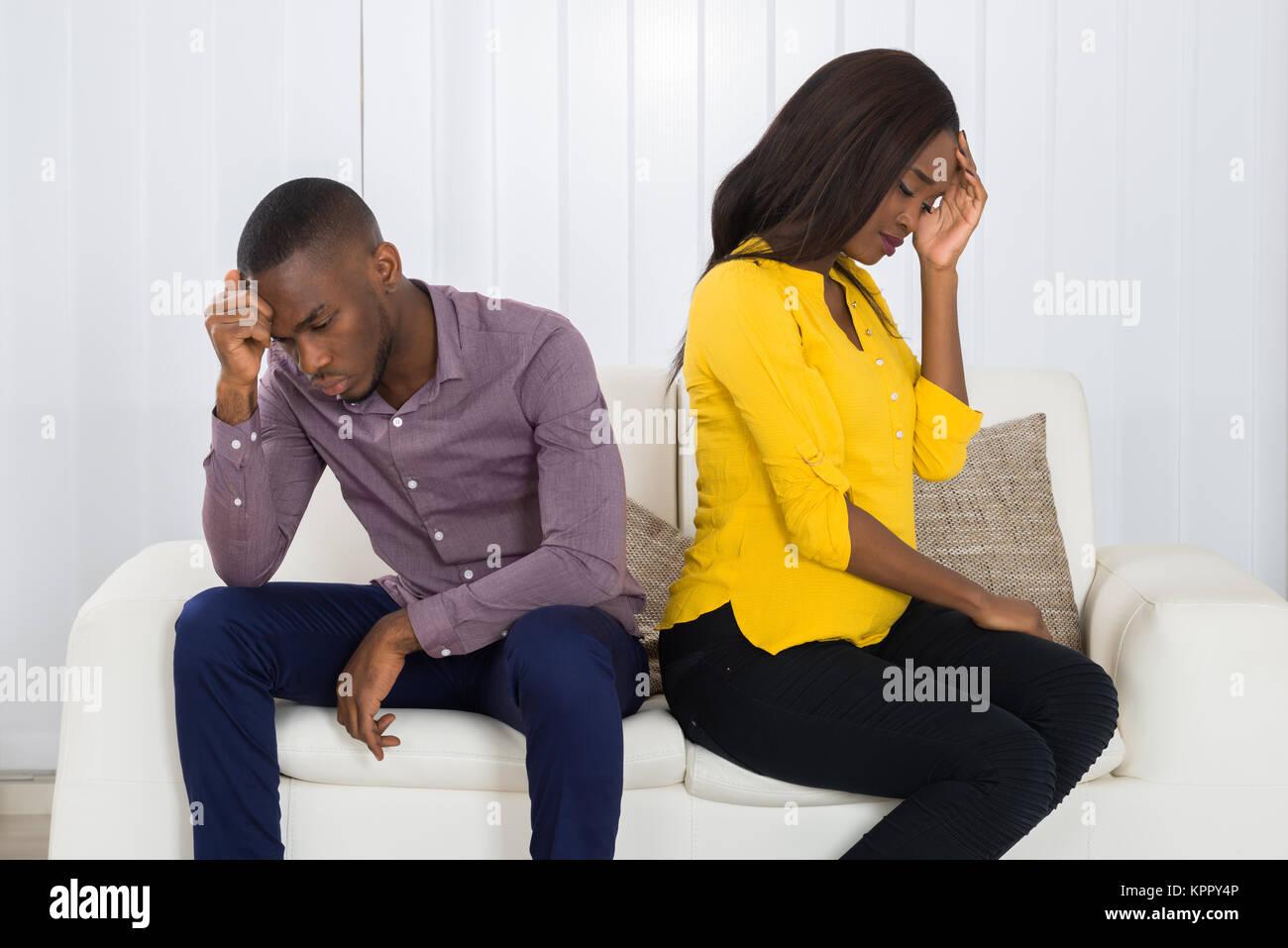 Couple Sitting Back To Back On Sofa - Stock Image
