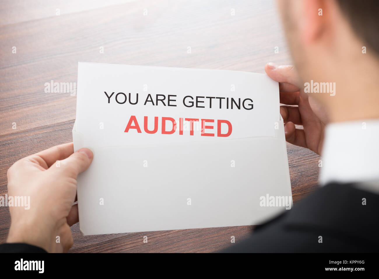 Businessman Opening Audit Letter In Office - Stock Image