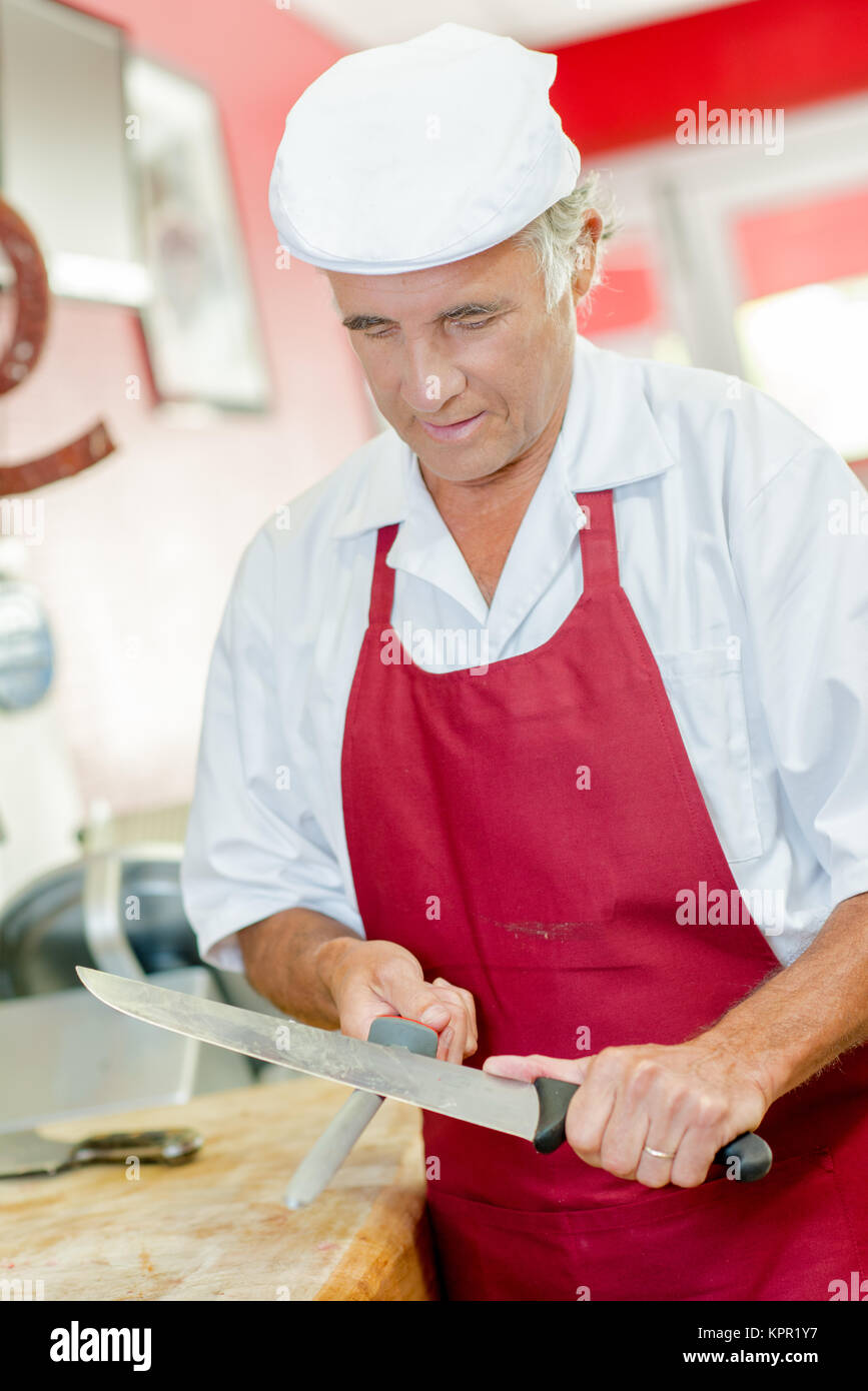 Butcher sharpening a knife - Stock Image