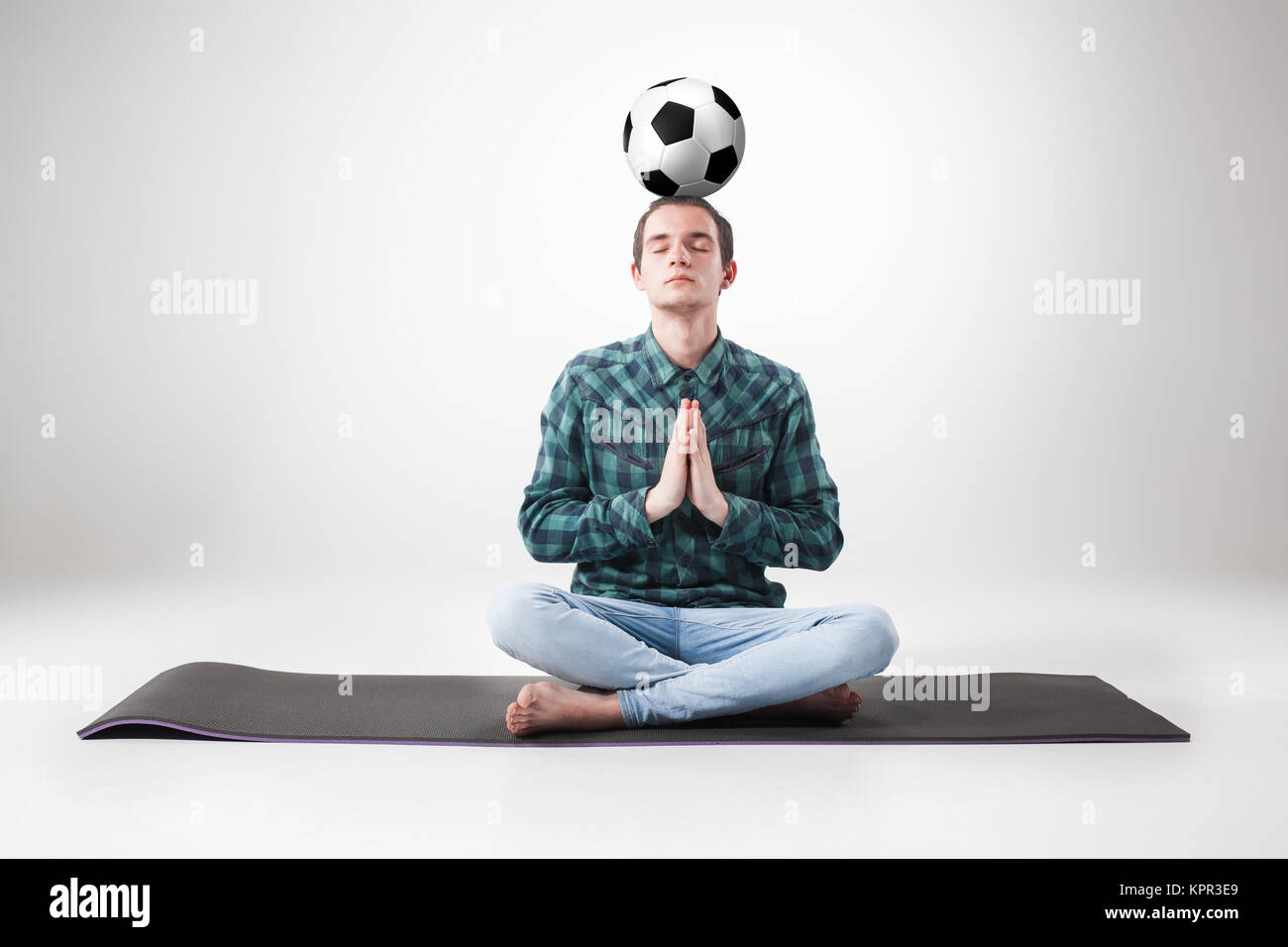 Portrait  of young man, practicing yoga with football ball - Stock Image