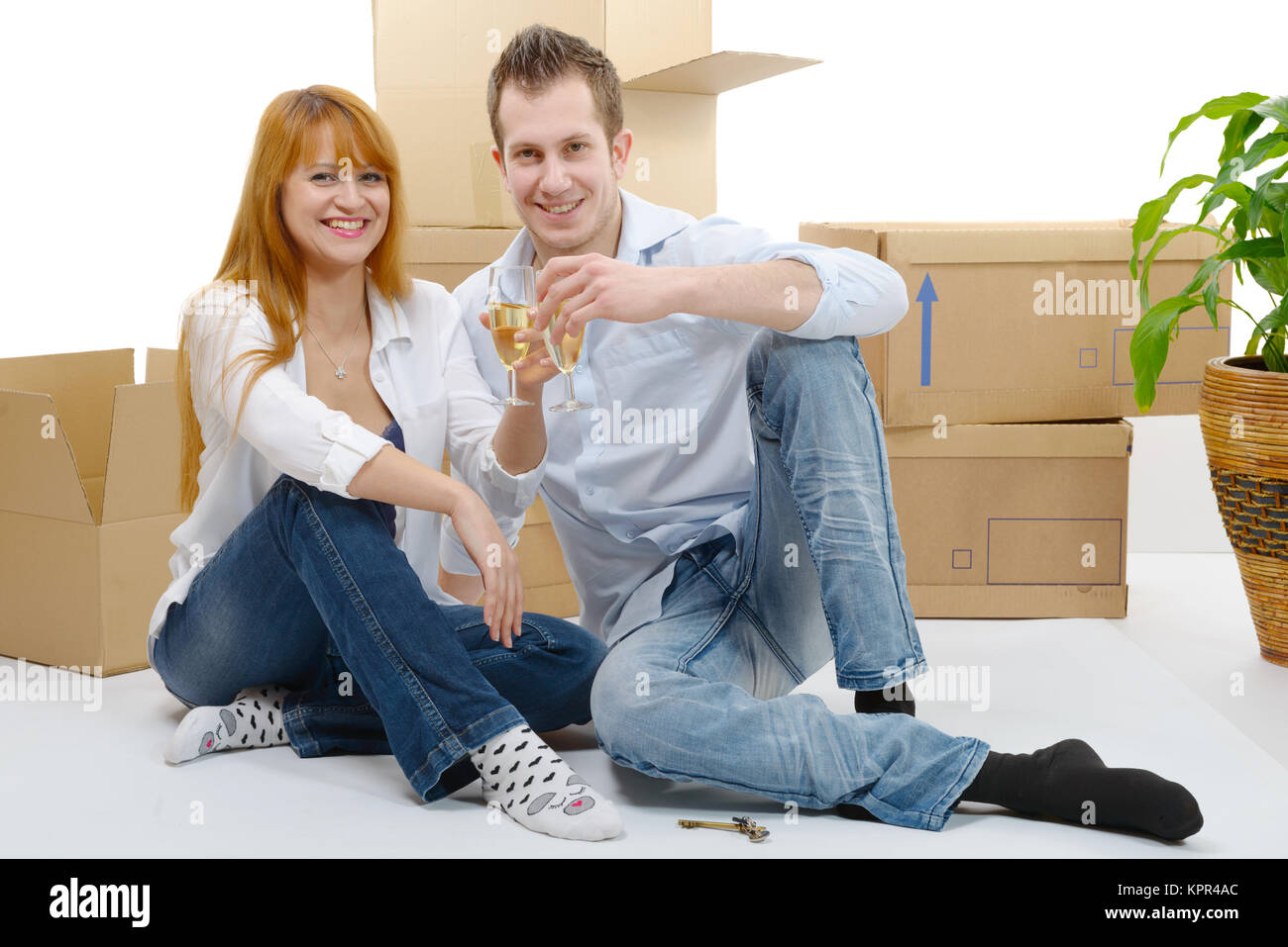 couple celebrating their new home,  and champagne in hand. - Stock Image