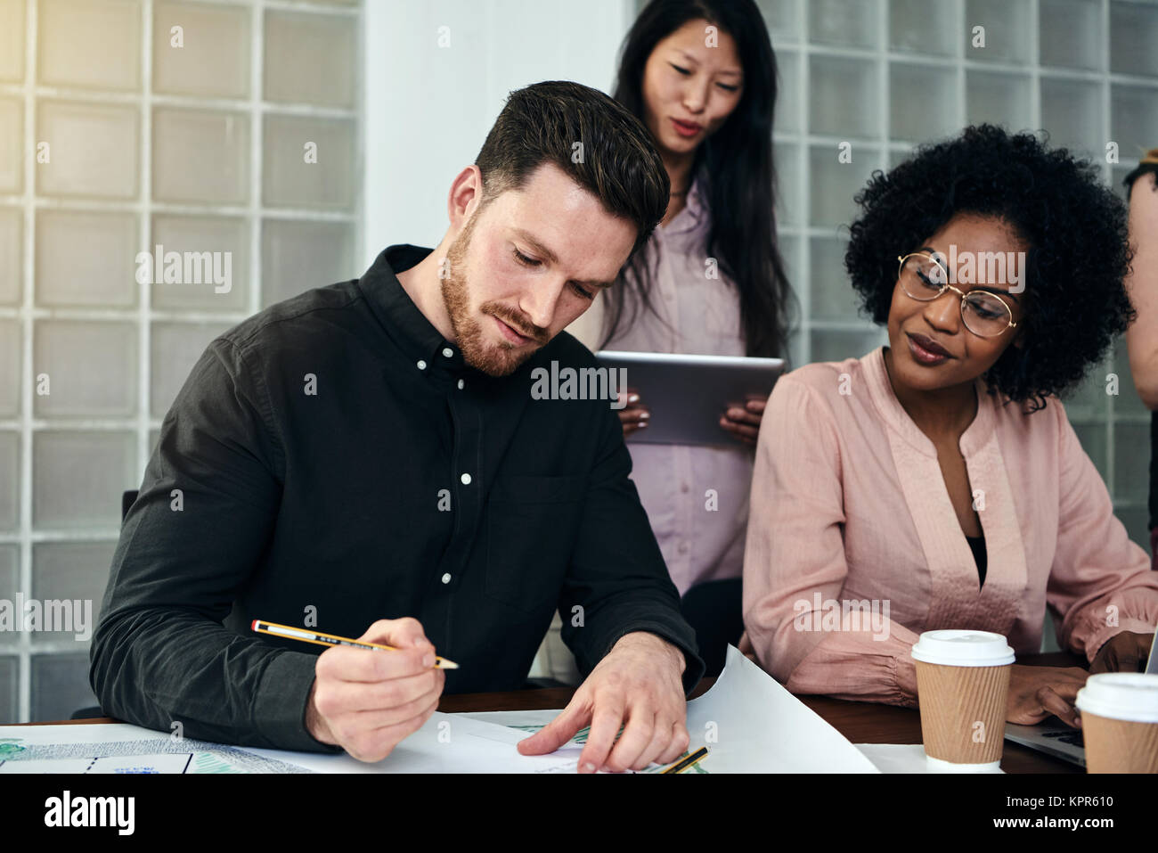 Young male architect working on a blueprint at a desk in a modern office with colleagues in the background Stock Photo
