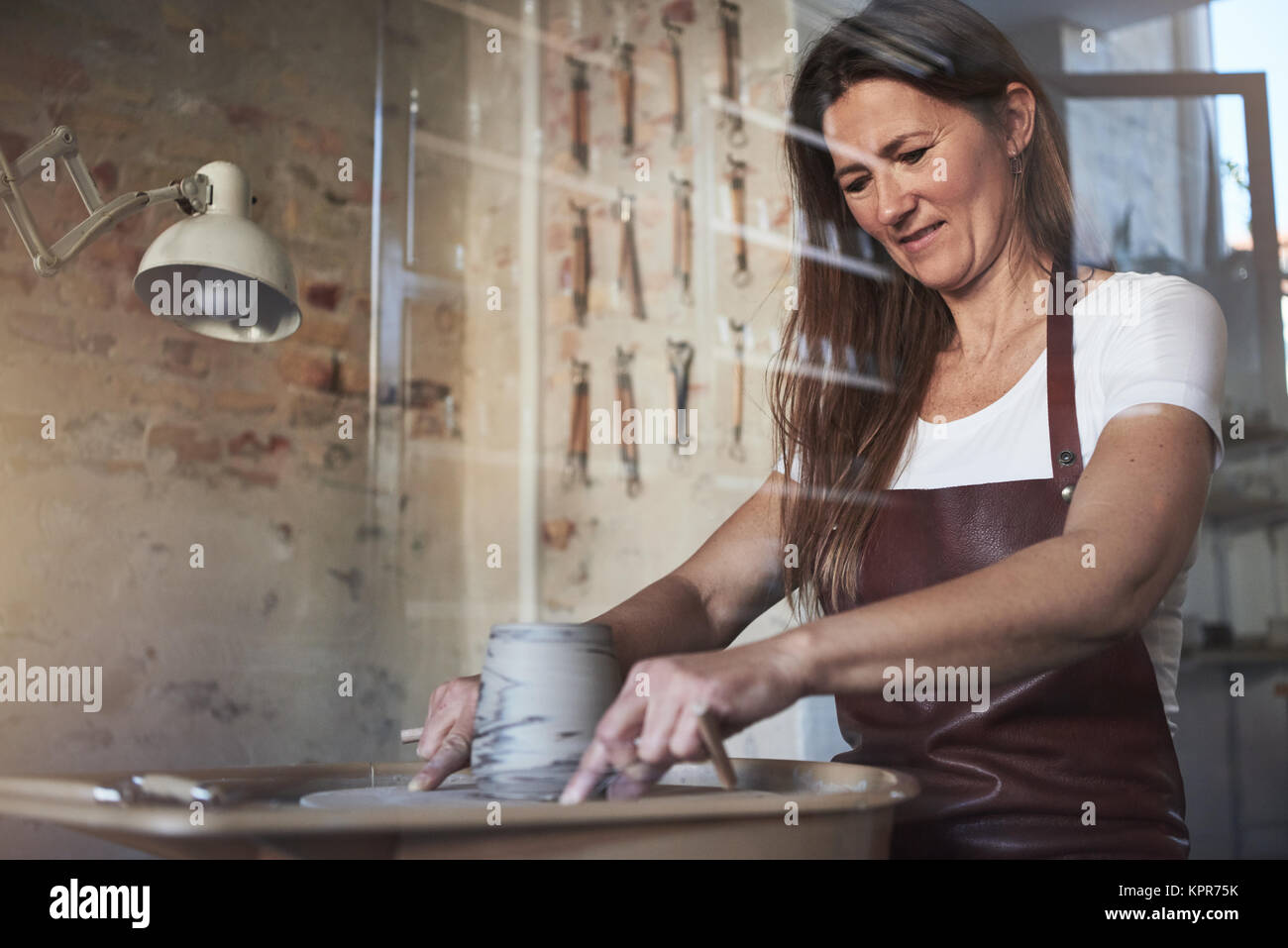 Female artisan creatively shaping a piece of clay turning on a pottery wheel while working in her ceramic studio - Stock Image