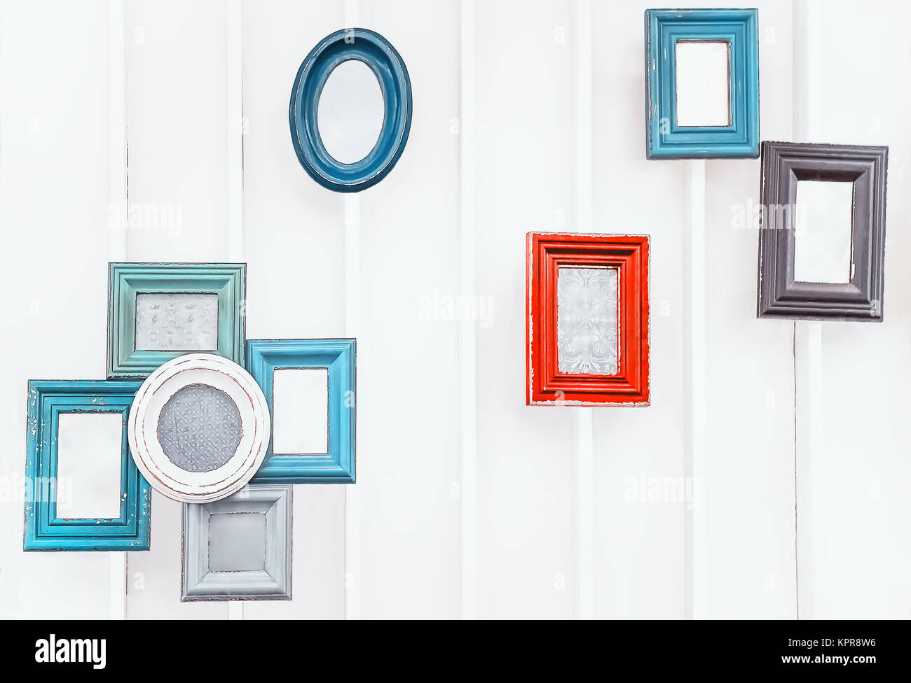 Vintage colorful photo frames on the white wall - Stock Image