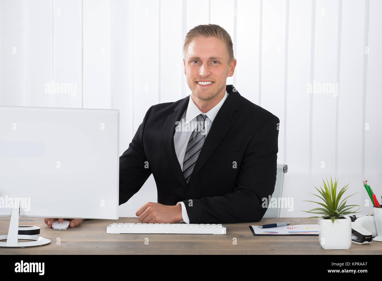 Businessman Smiling At Work In Office - Stock Image