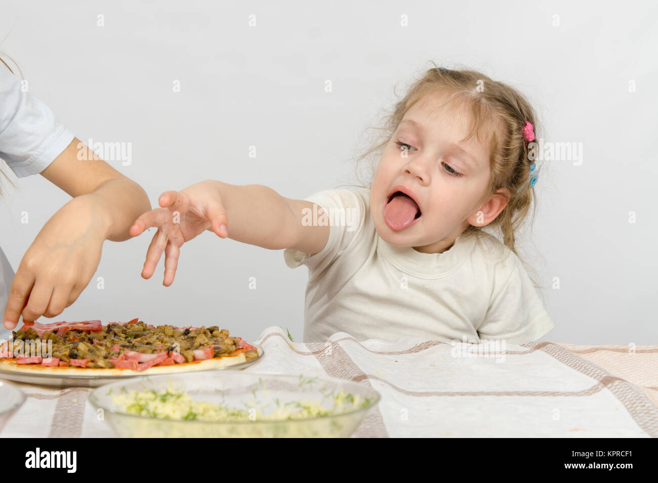 Little girl with tongue sticking out a hand to pull the pizza, which prepares her older sister Stock Photo