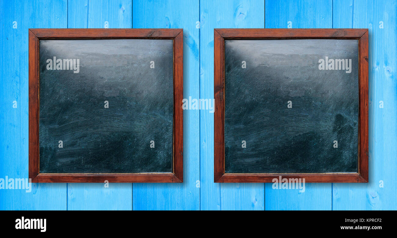 Blank wooden frames on the wall. Blackboards inside and light blue background, space for text. - Stock Image