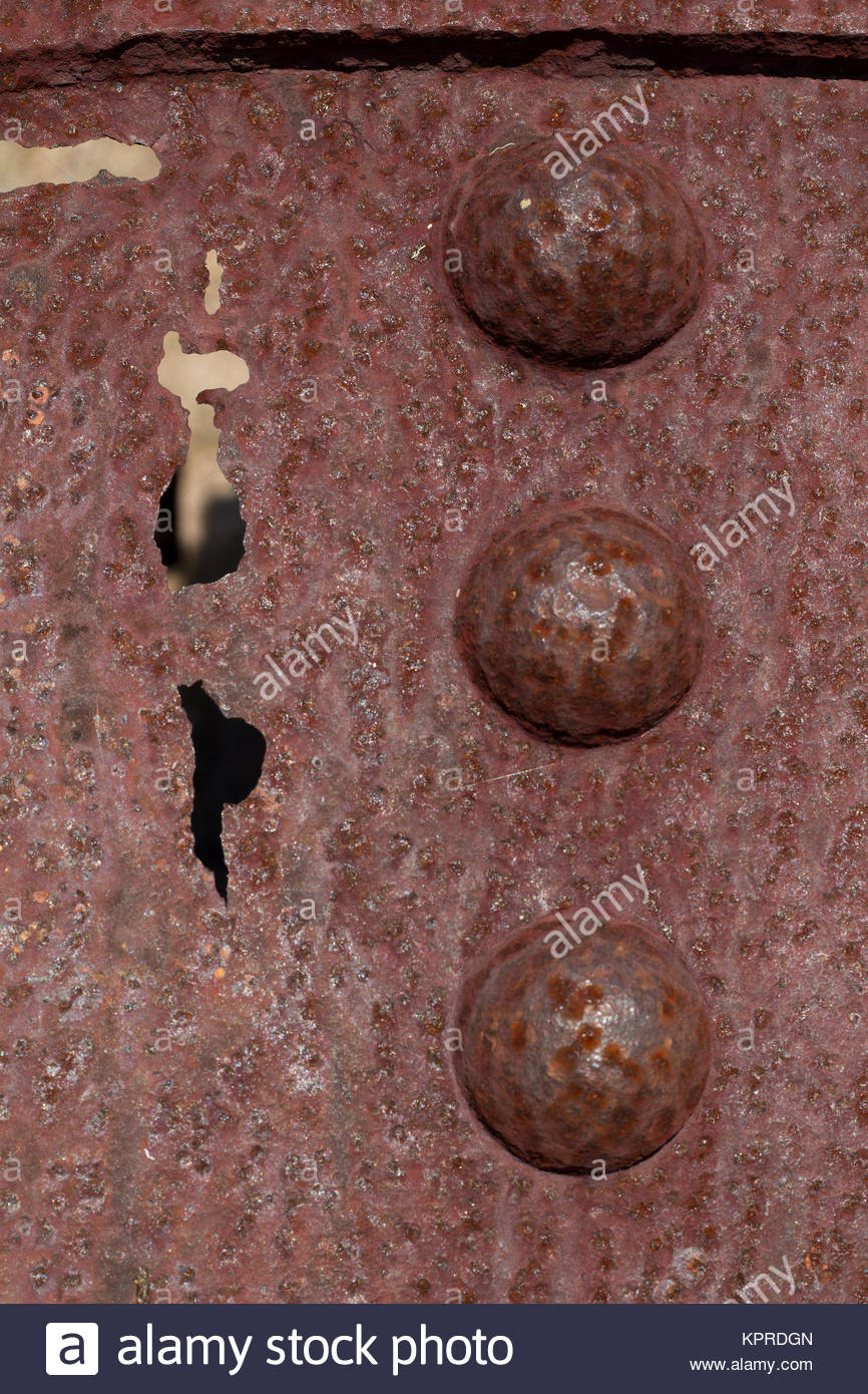 Rivets and a rusted hole in an old abandoned boiler in the Australian bush. - Stock Image