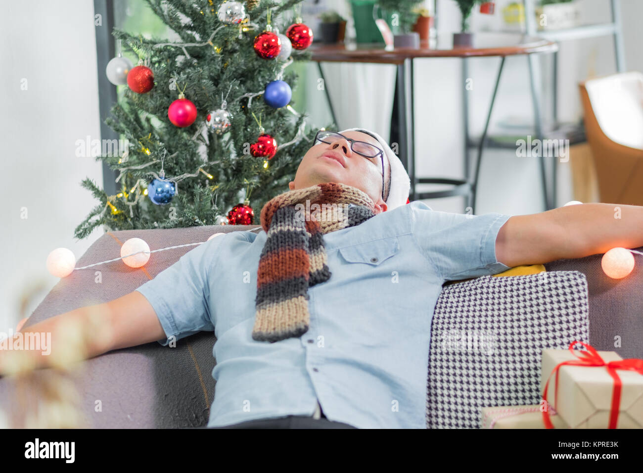 Asia man hangover and passed out sleep on sofa after heavy Christmas and new year party finish and lay on couch Stock Photo
