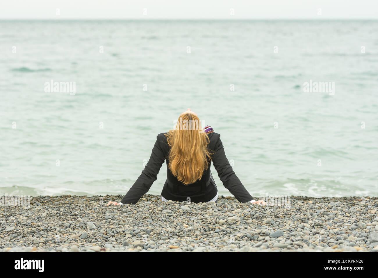 She sits back on a pebble beach by the sea on a cloudy day, his head thrown back Stock Photo