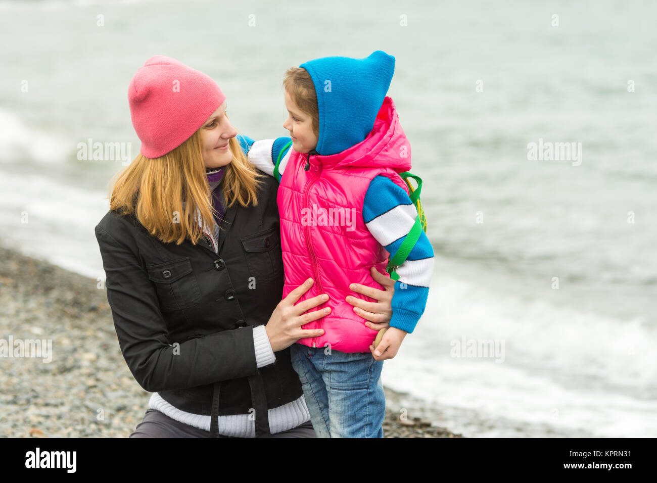 Mother hugging little daughter and tenderly looking at her on the beach in cold weather - Stock Image