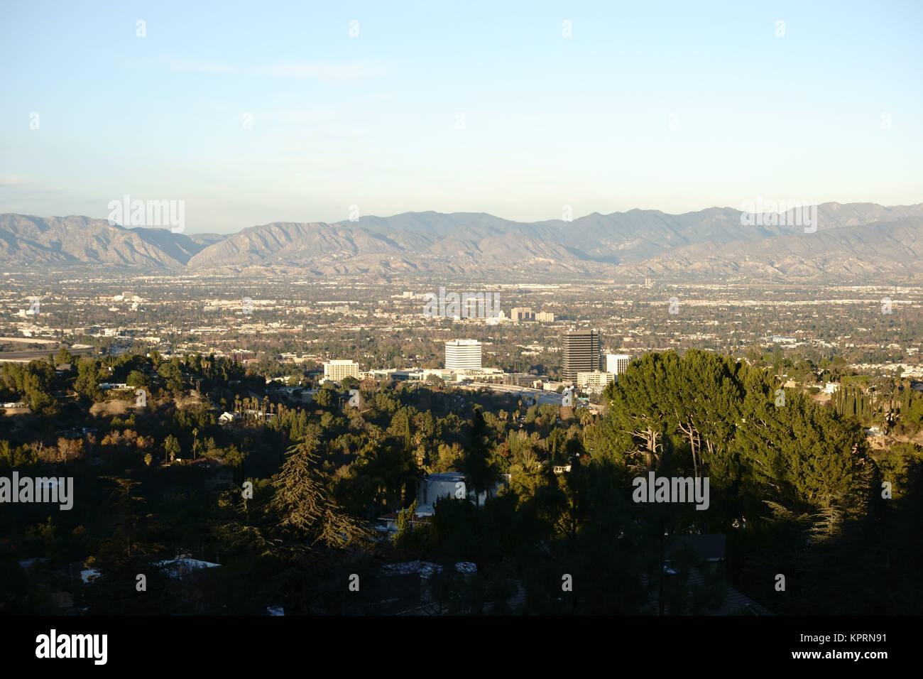 Die Skyline von Los Angeles mit wenigen Hochhäusern umgeben von einer hohen Menge von Parkanlagen, Bäumen - Stock Image