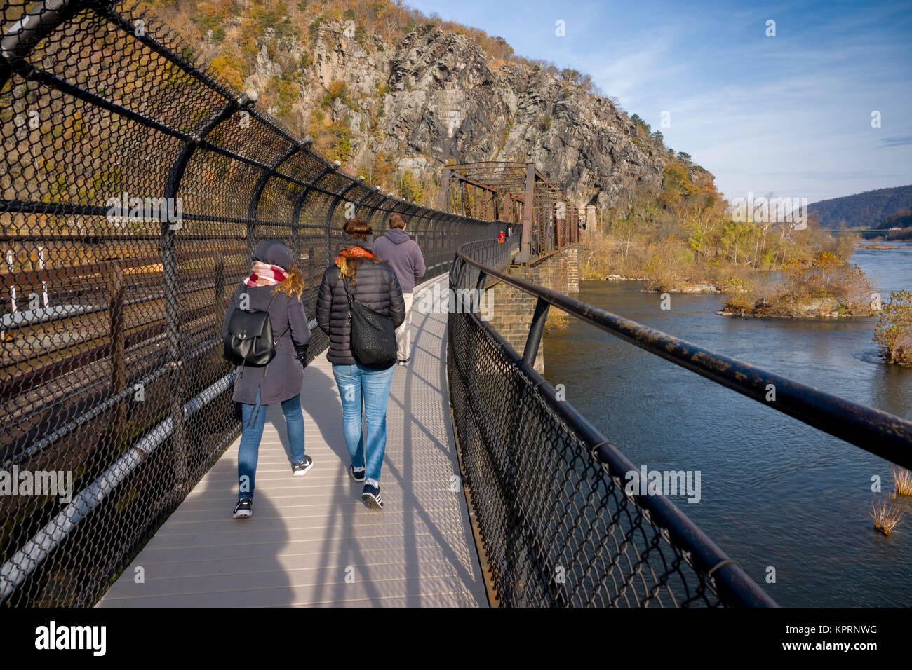 USA West Virginia WV hikers cross a train bridge that also carries the Appalachian Trail into Maryland - Harpers - Stock Image