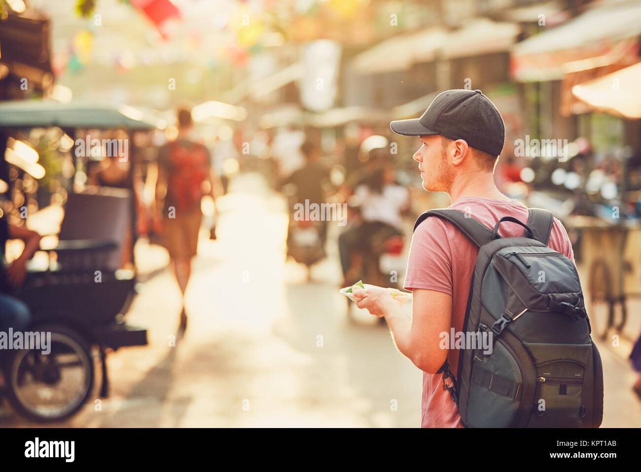 Young man (tourist)  with backpack walking to the night market buying tasty sweet food. Busy street full of restaurants, - Stock Image
