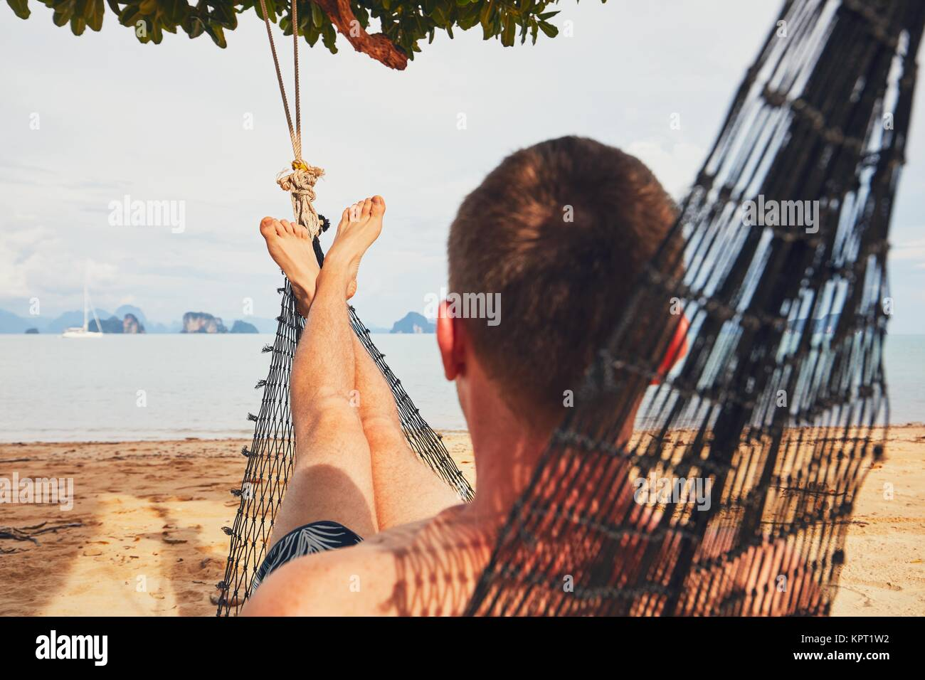 Young man (tourist) relaxing in the hammock on the sand beach - selective focus on foot. Koh Yao Noi island situated - Stock Image
