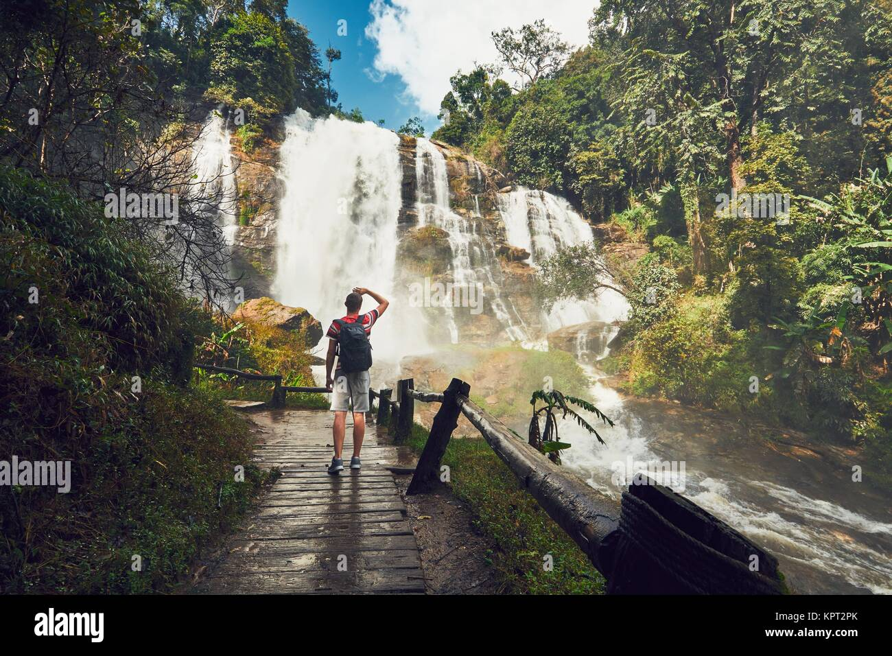 Young man (traveler) standing near Wachirathan waterfall in tropical rainforest. Chiang Mai Province, Thailand - Stock Image