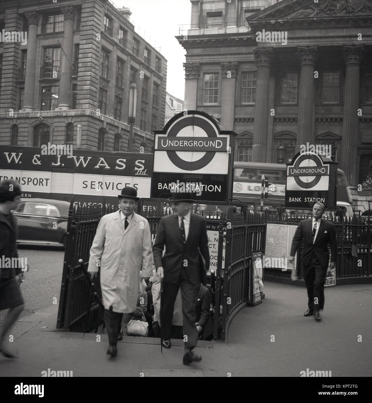 1950s, London, two city gentlemen wearing bowler hats emerge from the narrow exit at Bank Underground Station in - Stock Image