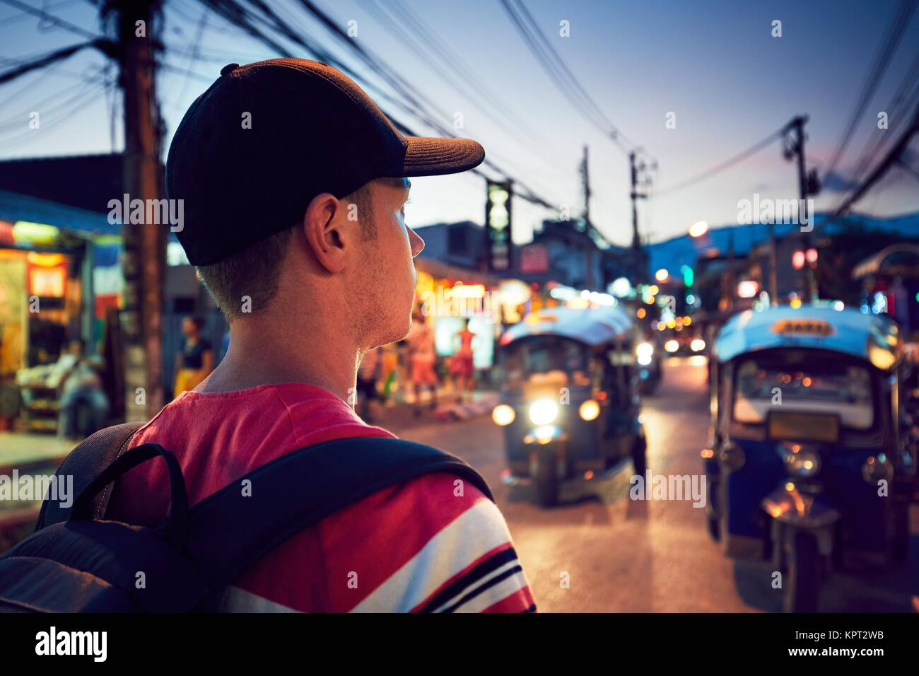Young man walking on the busy street full of shops - Chiang Mai, Thailand - Stock Image