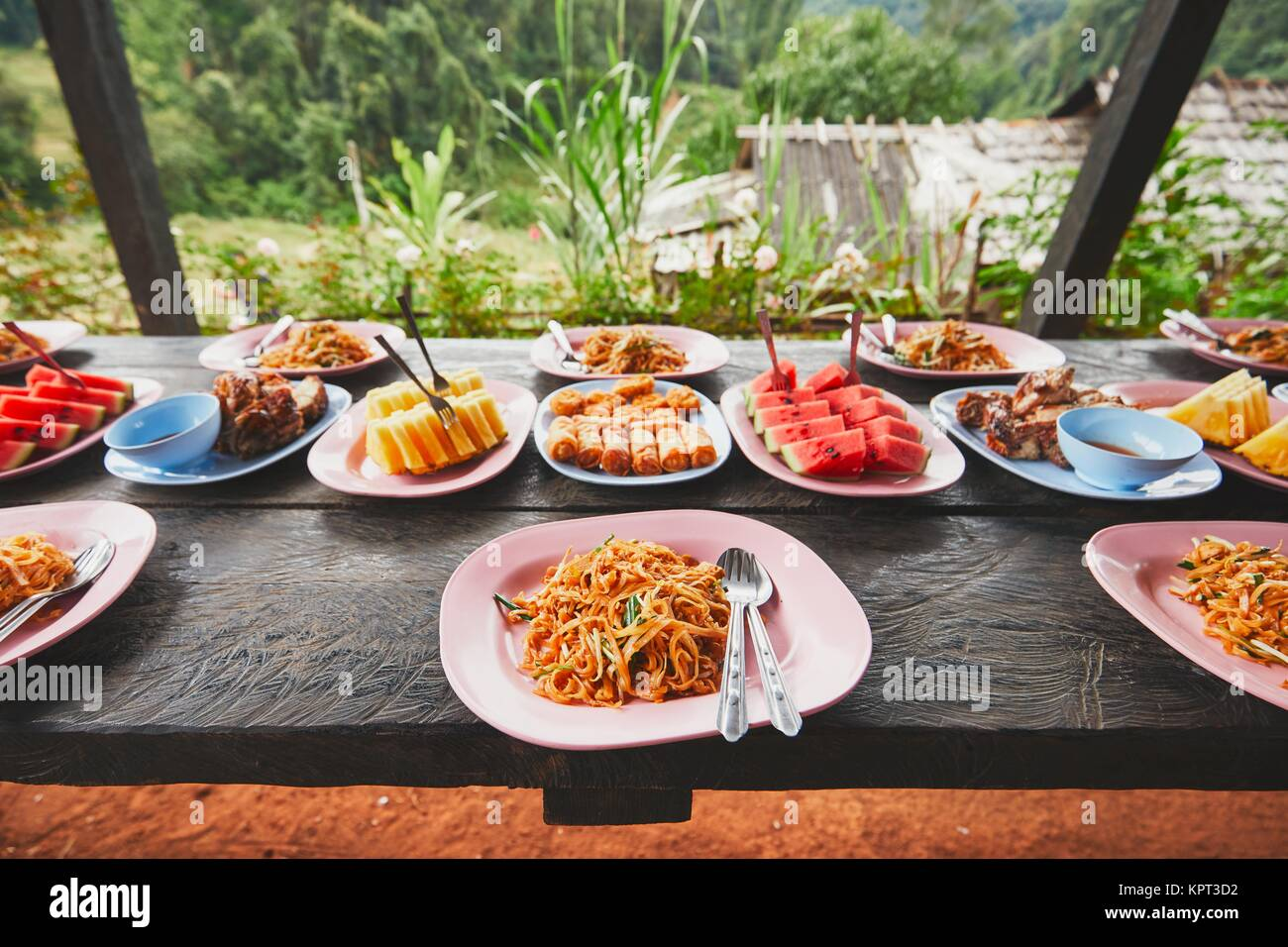 Lunch in the middle of the jungle. The table full of foods and fruits. Traditioal Pad Thai, spring rolls, melon - Stock Image