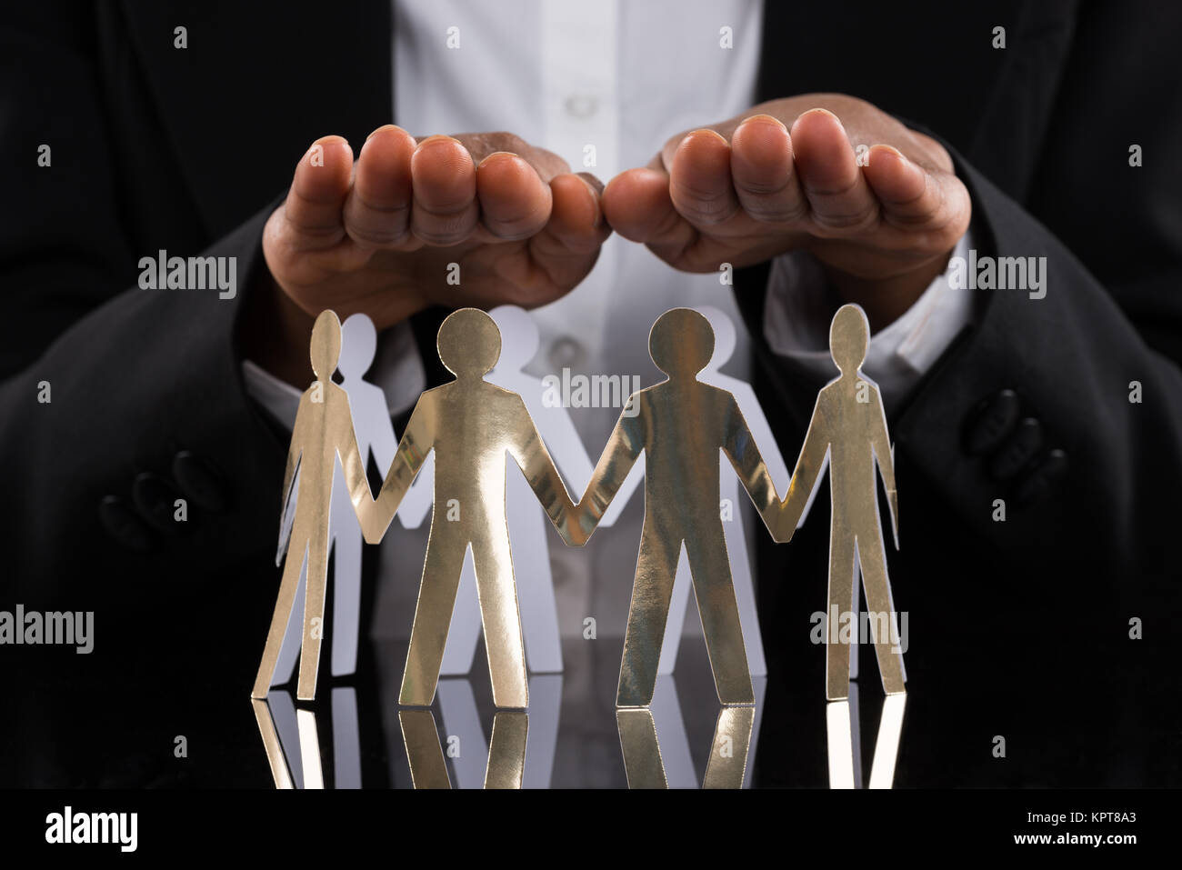 Businessperson Protecting Cut-out Figures - Stock Image
