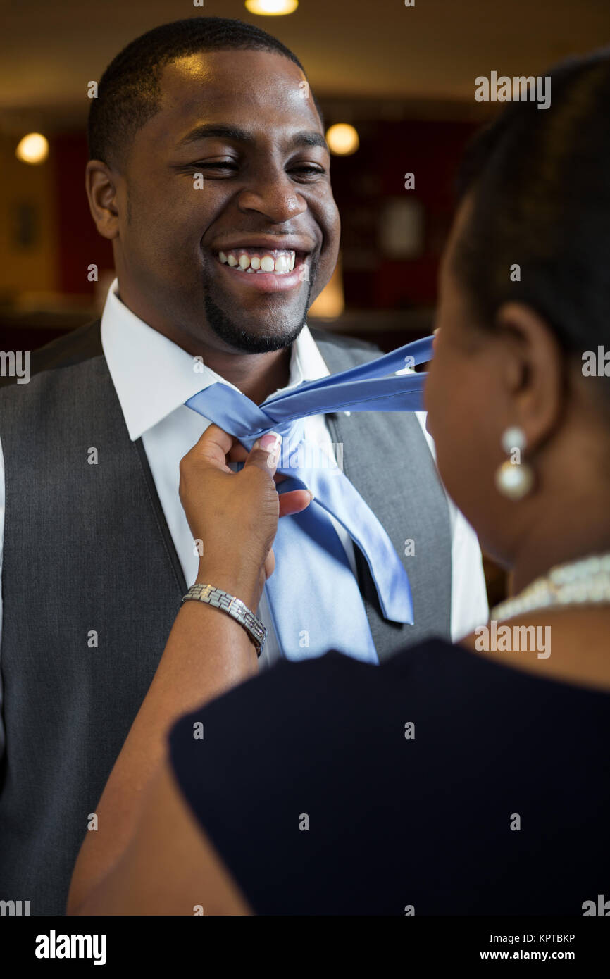 Mother helping her son tie his tie. Stock Photo