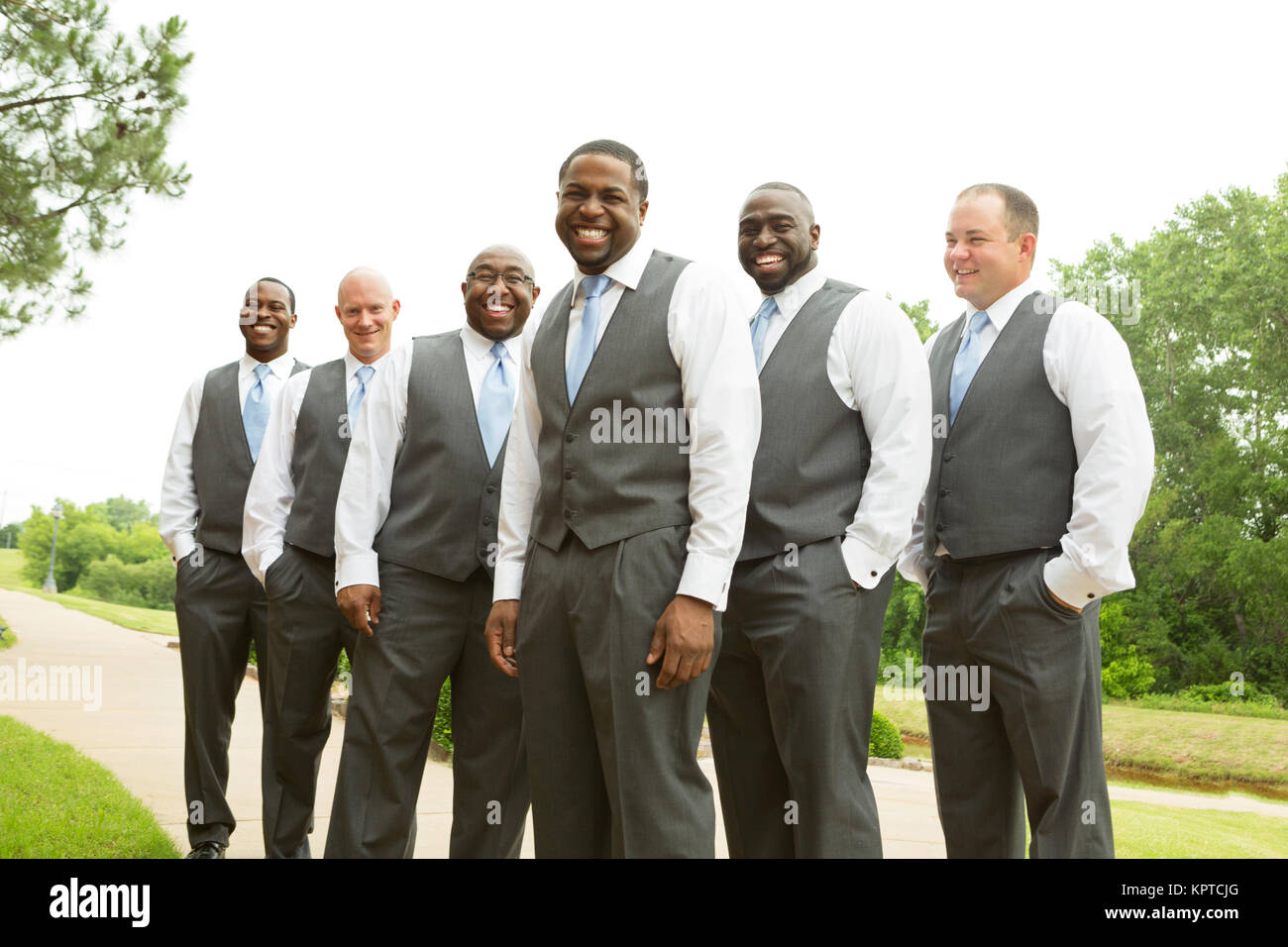 Groom and groomsmen smiling at a wedding. Stock Photo