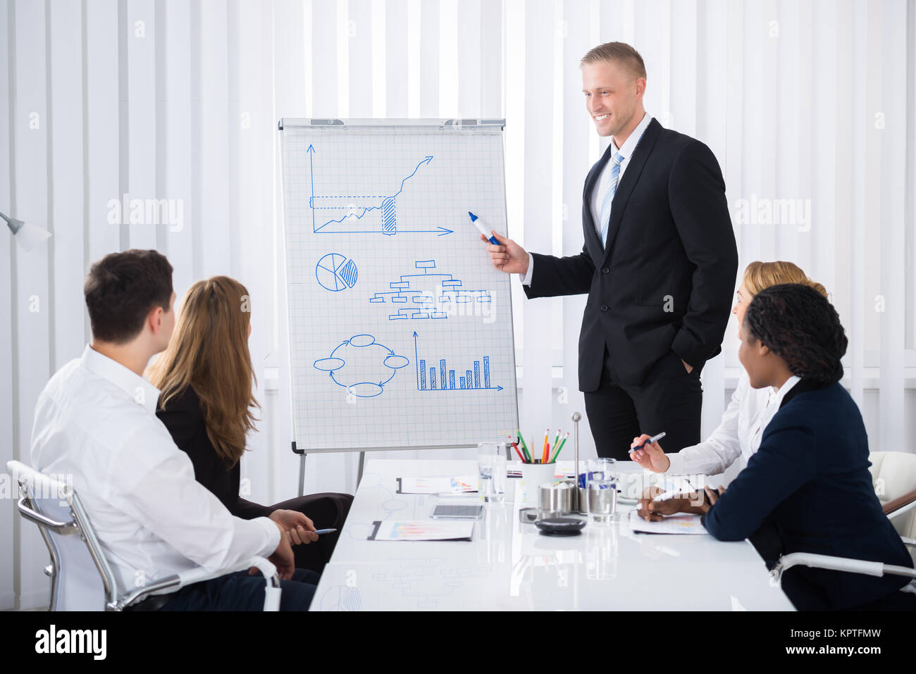 Businessman Giving Presentation To Businesspeople - Stock Image