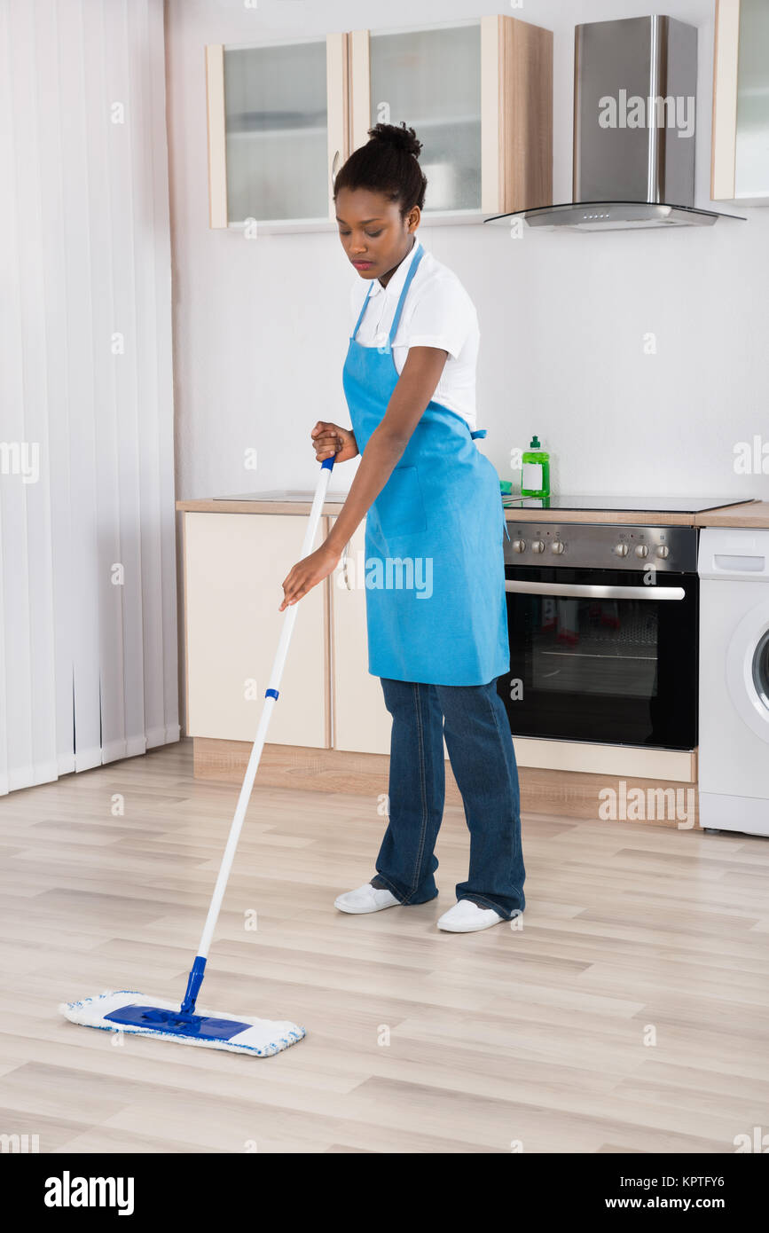 Female Janitor Mopping Floor In Kitchen - Stock Image