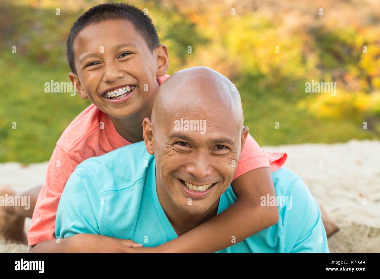 Father playing with his kids on the beach. - Stock Image