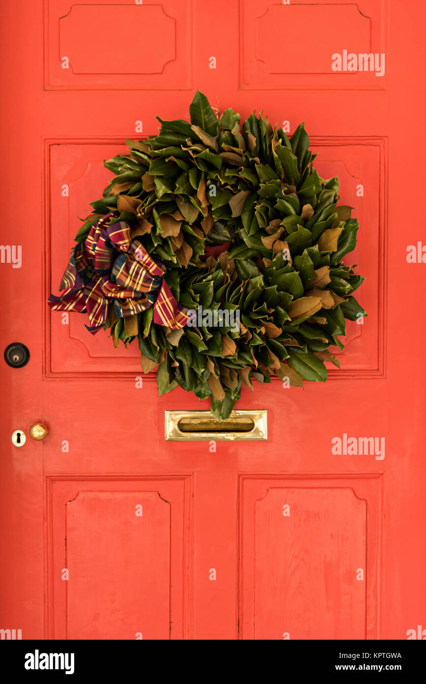 The Wooden Doorway Of A Historic Home Decorated With A Magnolia Leaf