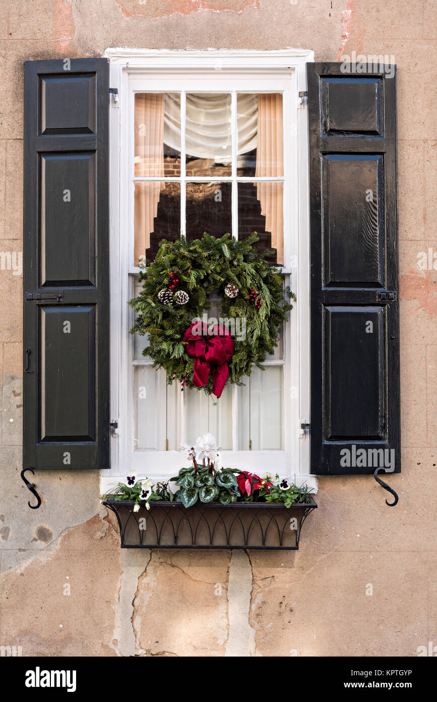 The window of a historic home decorated with a Christmas wreath and window box on Meeting Street in Charleston, - Stock Image