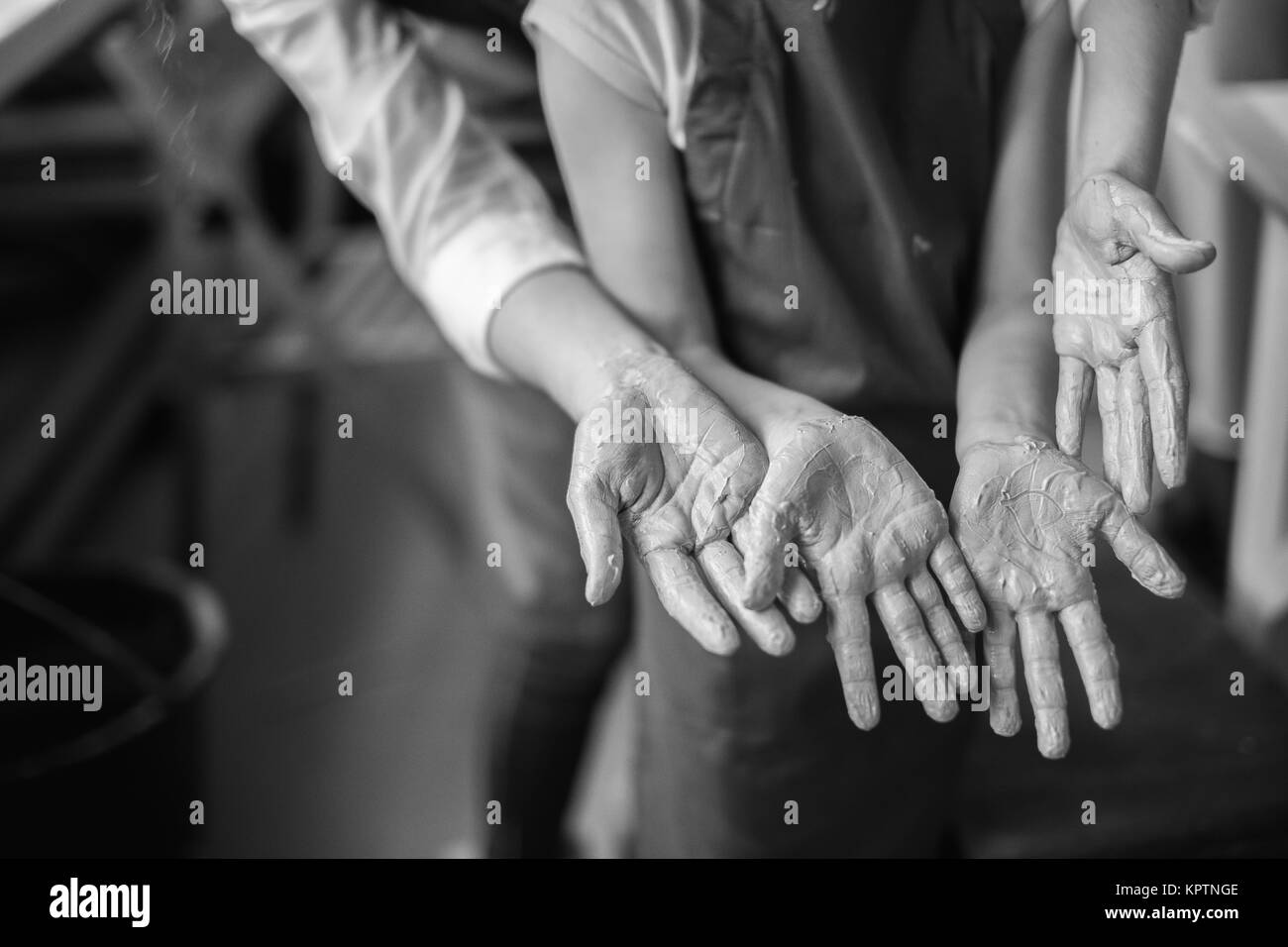 Potter's hands and children's hands in clay - Stock Image