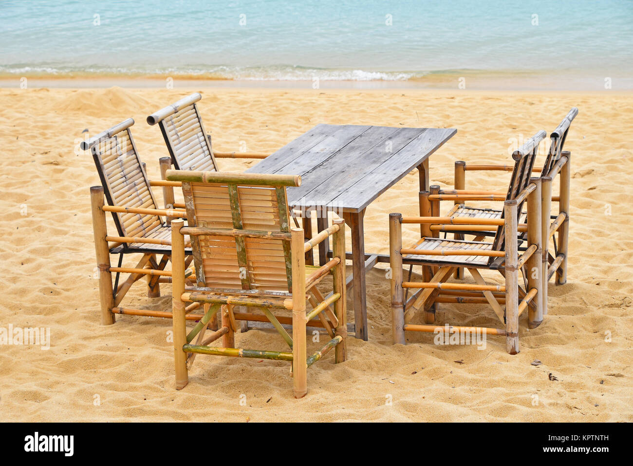 Wooden Bamboo Furniture, Table And Five Chairs Around On San Beach With  Blue Sea Water