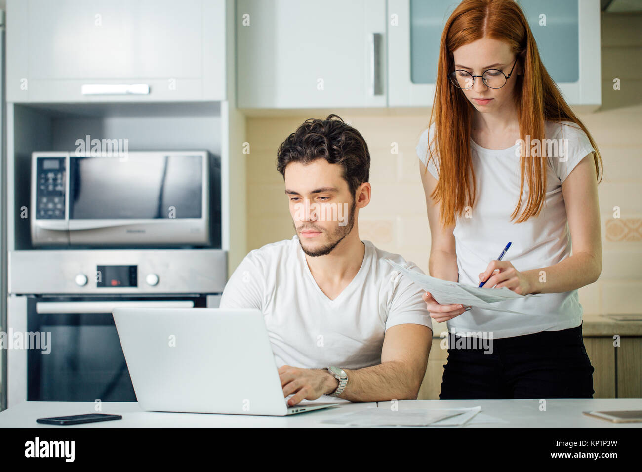 woman calculate or write accounts with pen, her husband using laptop - Stock Image