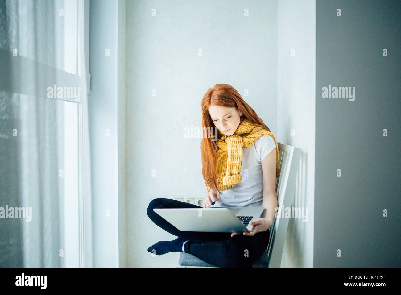 young woman using laptop at home - Stock Image