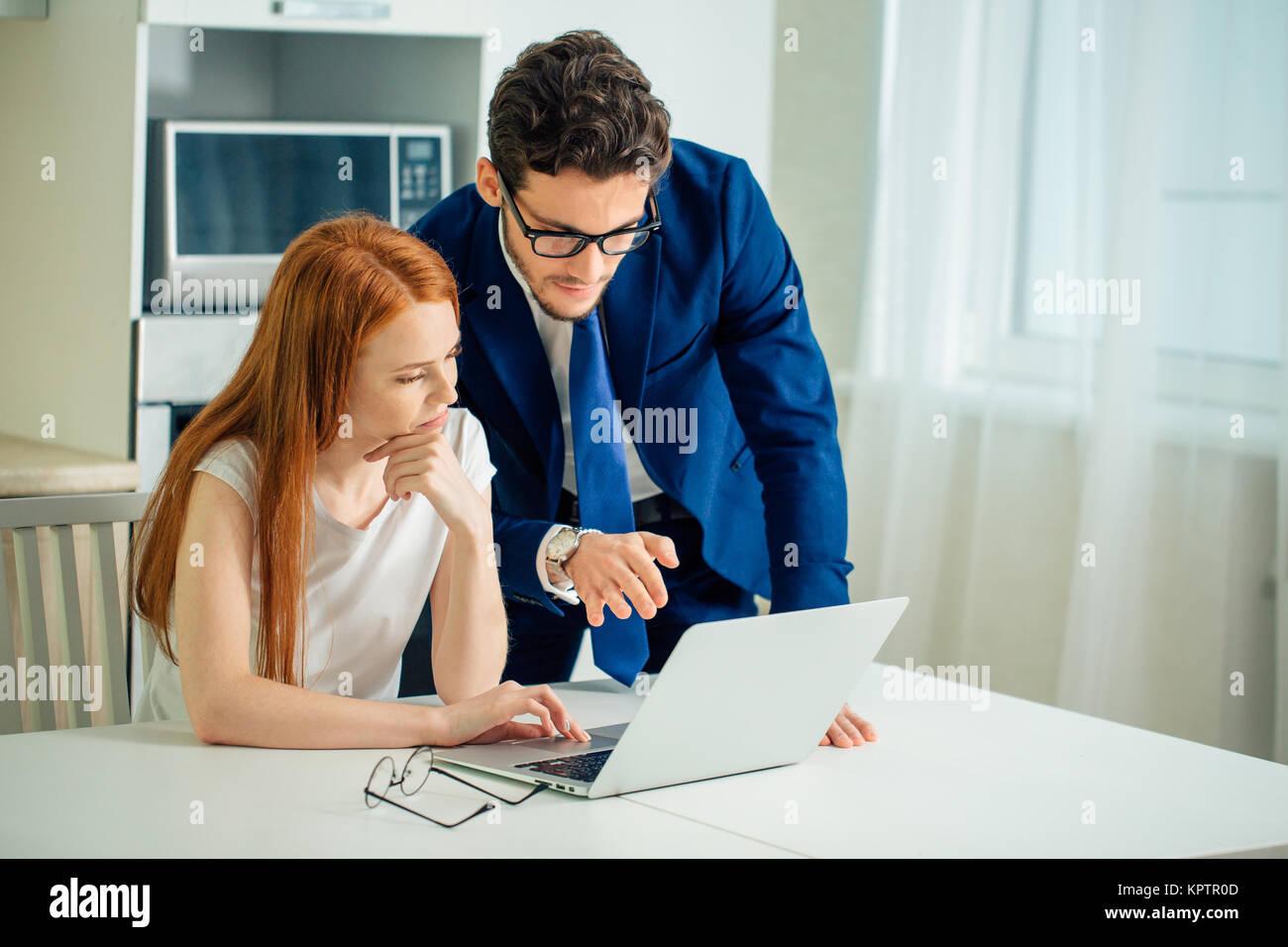 Business man explaining something to woman with laptop - Stock Image