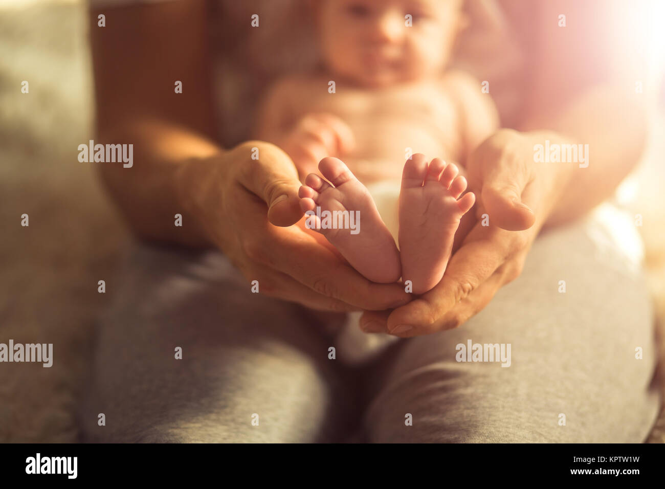 Mother holds newborn baby's feets. Tiny feet in woman's hand. Stock Photo