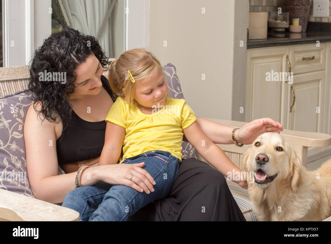 Mother and Daughter with Golden Retriever on Porch Stock Photo