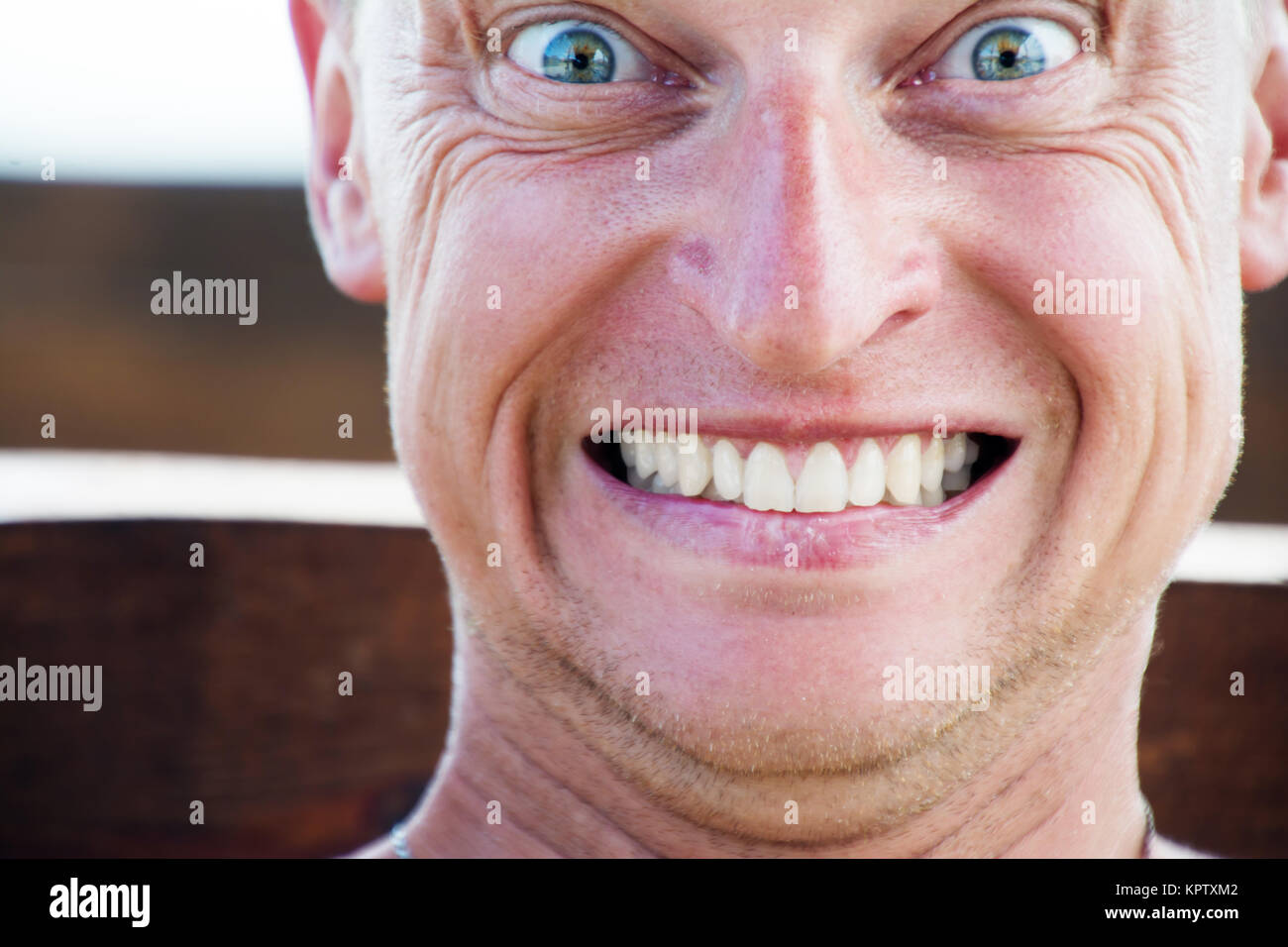 Close up portrait of funny man, grins his teeth. - Stock Image