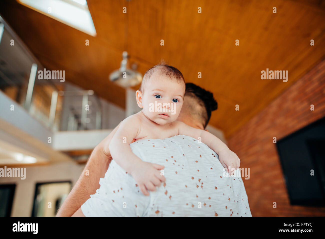 baby boy on father's shoulder - Stock Image