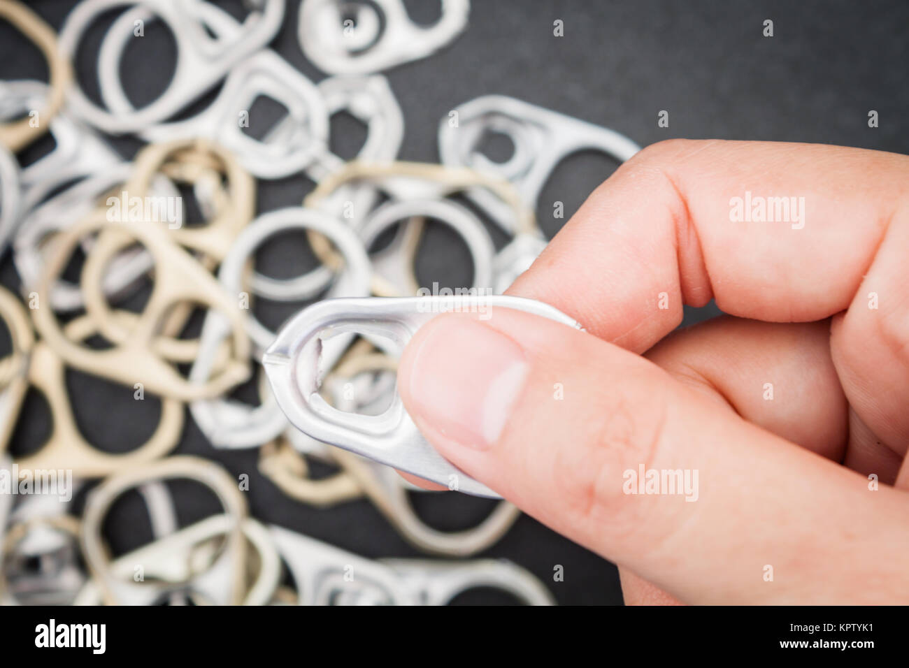 Woman hand holding ring pull cans opener background - Stock Image