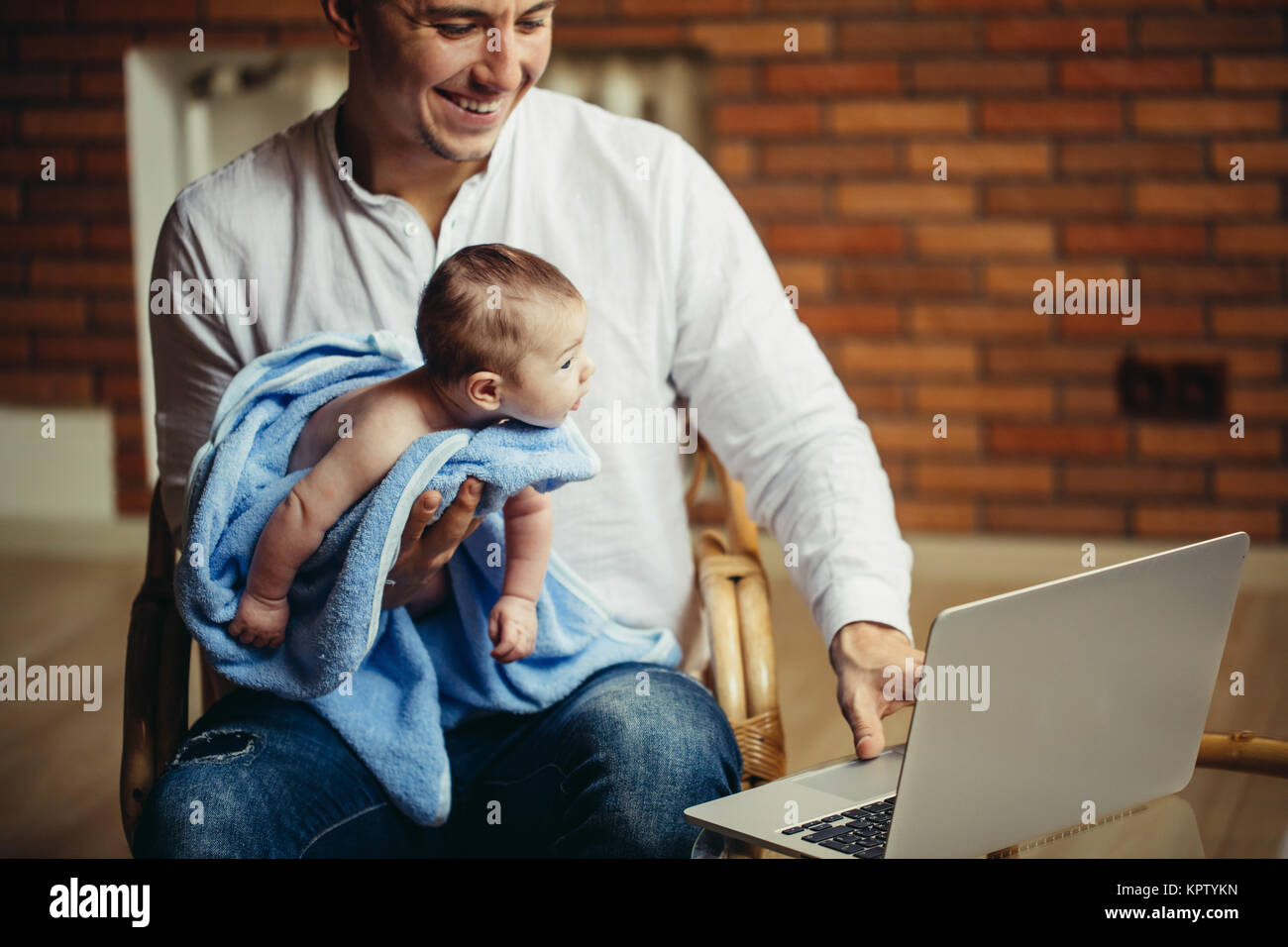 man working at desk at home with laptop, holding cute babys, looking at screen - Stock Image